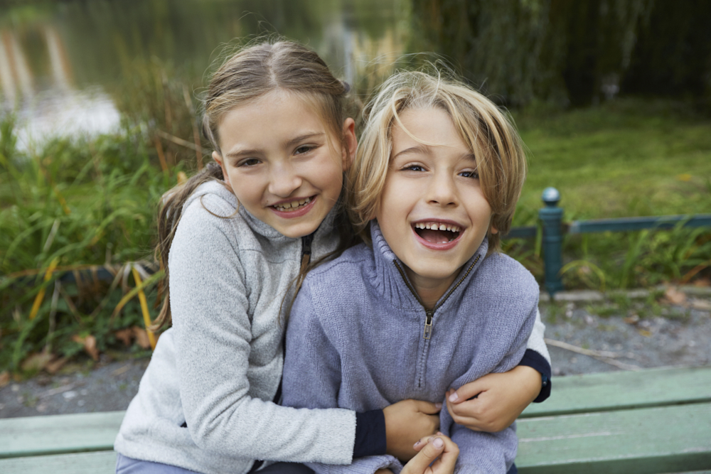 spaßiges Kinderpotrait, Kinder kuscheln miteinander, Kinder kucheln draußen in der Natur,