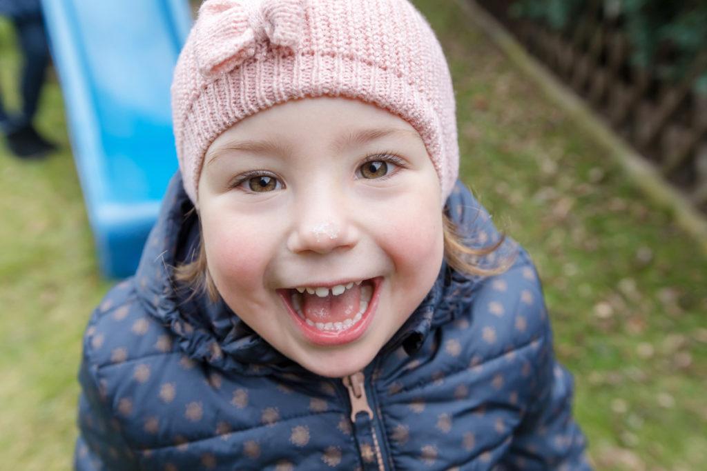 lachendes Mädchen mit Schneeflocke auf der Nase