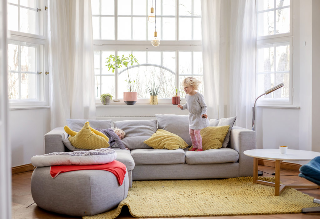 Zwei Mädchen hüpfen auf dem Sofa