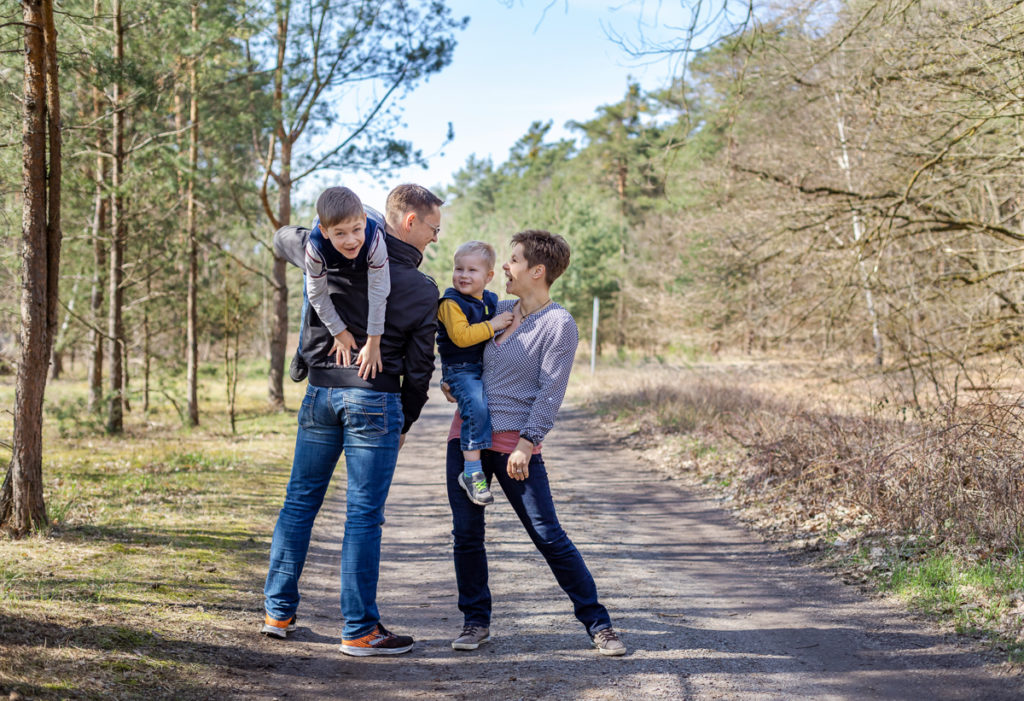 Familienfoto im Wald mit hüpfenden lachenden Eltern