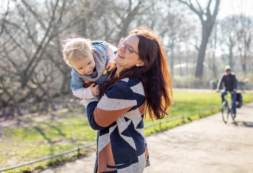 Mama mit Tochter auf dem Arm lachen