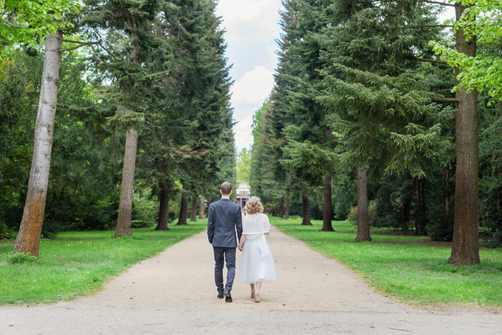 Brautpaar läuft durch Baumallee