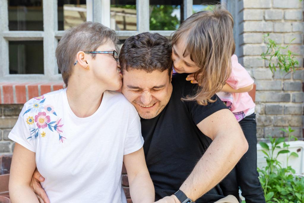 Mama und Mädchen knutschen Papa ab