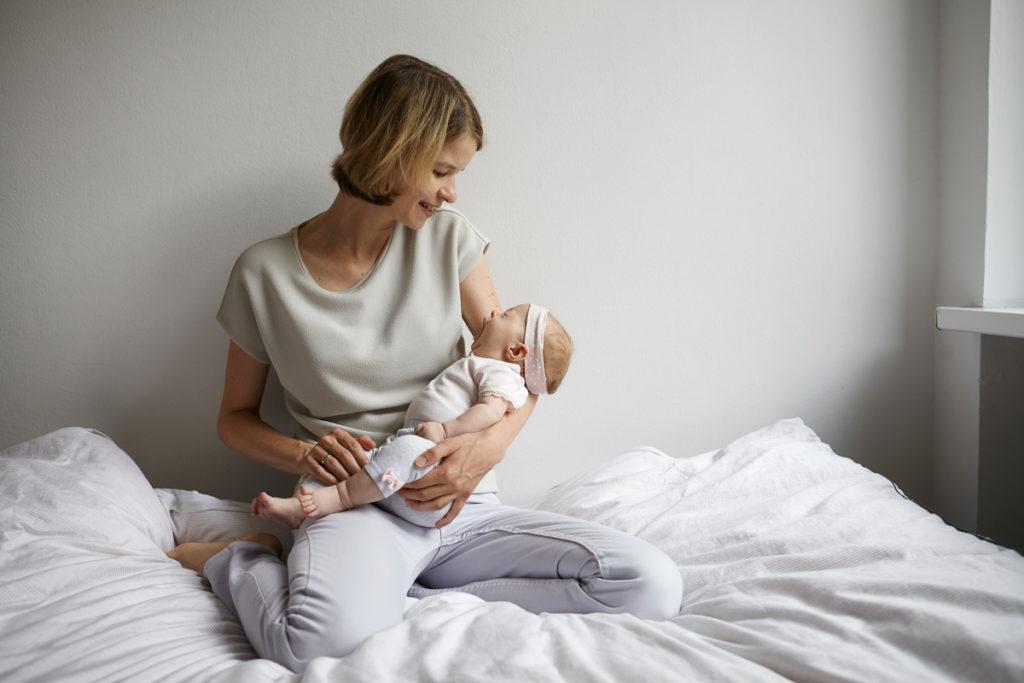 Mama mit Baby auf dem Arm im Bett