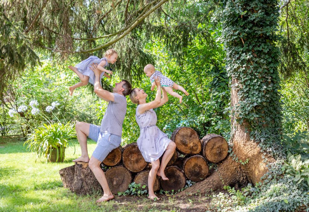 Eltern unter einem Baum sitzend und ihre Kinder hoch hebend