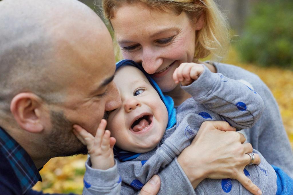 lachendes Kind in den Armen von Mama und Papa