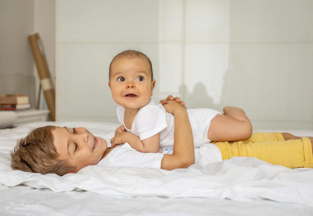 Babyfotos im ersten Jahr, Geschwisterchen liegt auf dem Bauch seines Bruder