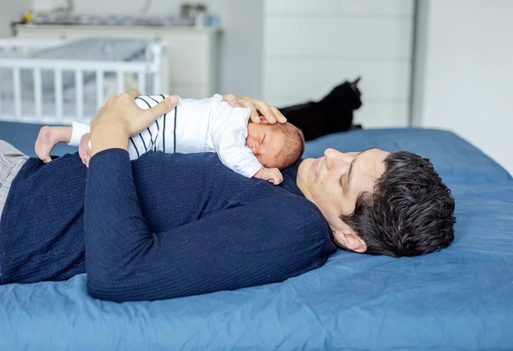 Baby und Papa kuscheln auf dem Bett, Babyshooting im ersten Jahr, neugeborenes Shooting mit Papa