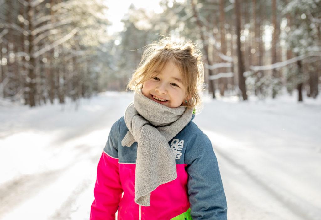 coole Familienfotos, Kind lächelt im Winter portrait,