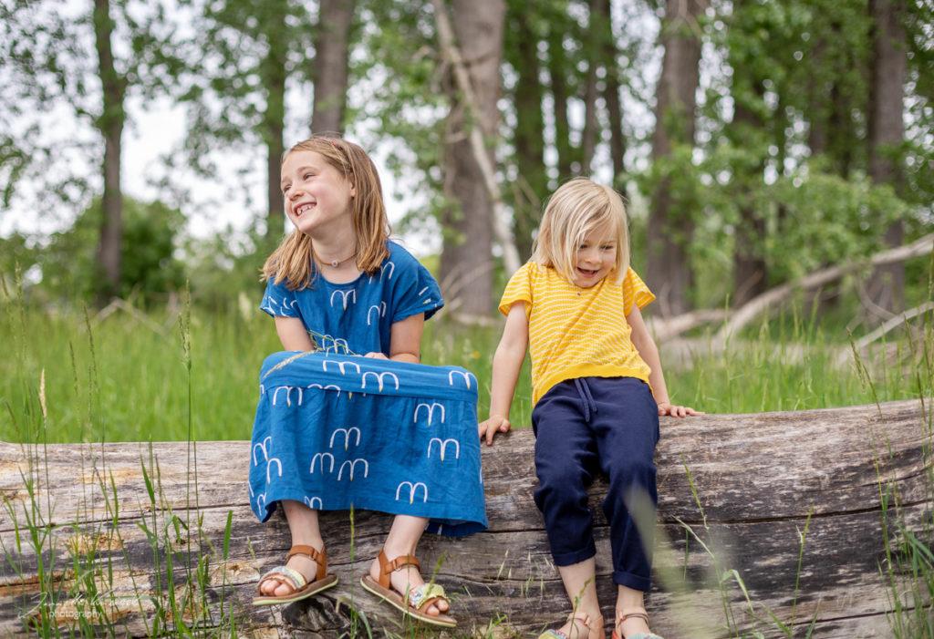 Kinder Fotoshooting im Wald, Kinder sitzen auf einem Baumstamm