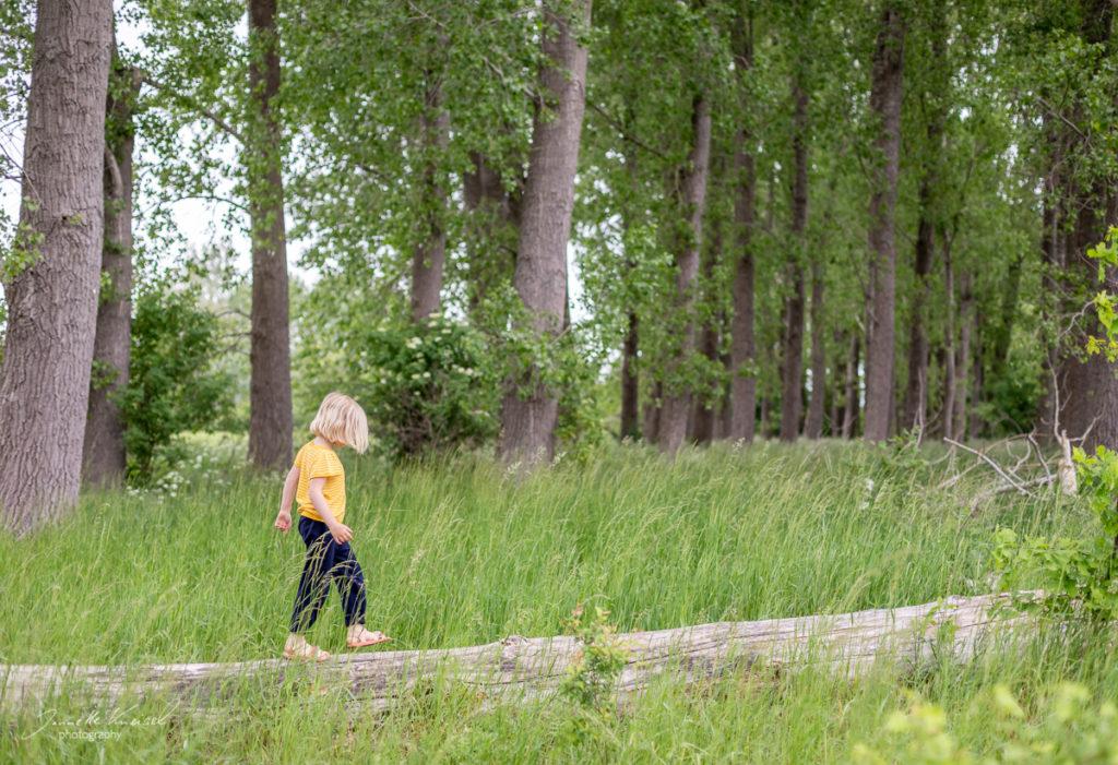 Kind balamziert auf Baumstamm, Shooting in der Natur